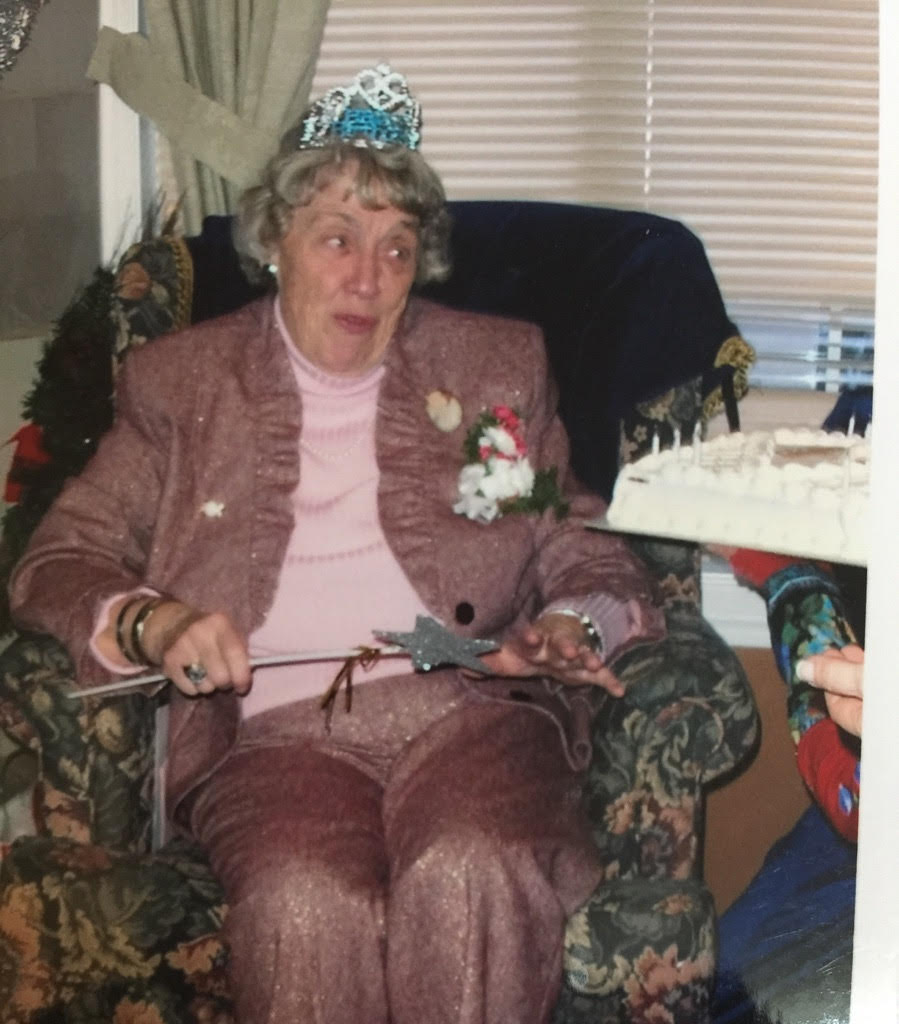 Mom in tiara on chair at 80th birthday