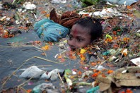 child in water with plastic garbage