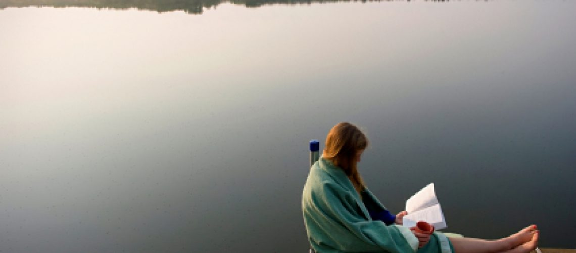 photo of woman reading by lake