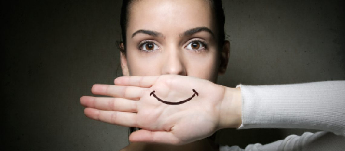 sad woman with happy face on hand